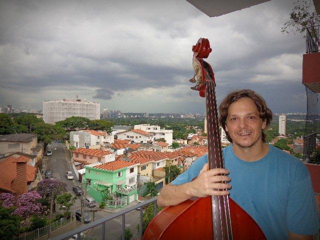 O contrabaixista Zéli Silva, na sacada de seu apartamento, e São Paulo (foto: Carlos Bozzo Junior)