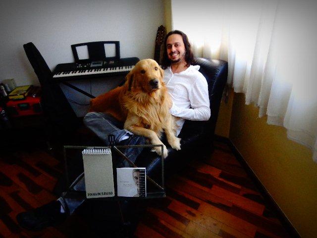 """O músico Chrystian Dozza ouvindo o CD """"Dois Destinos """", acompanhado de seu cão John Downland (Foto: Carlos Bozzo Junior)"""